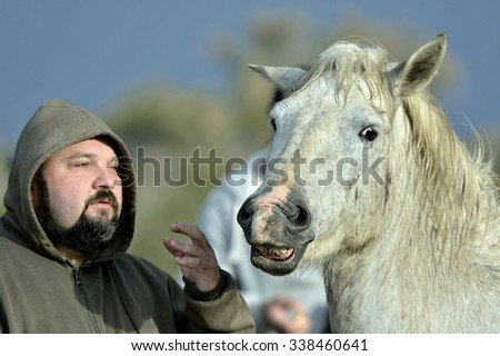 Man speaking to a Horse. Horse - the interlocutor. the person with a beard in a hood talks to a white horse - stock photo