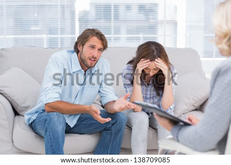 Man speaking to the therapist while her wife cries next to him - stock photo