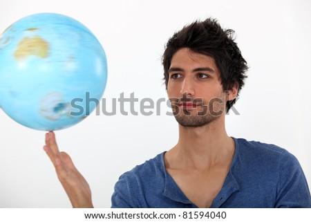 Man spinning a globe - stock photo