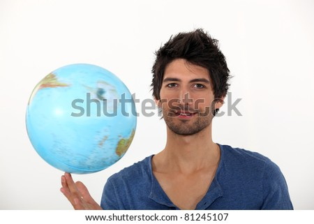Man spinning a globe on his fingertips - stock photo