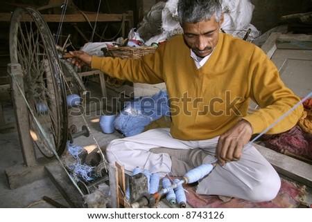 man spinning the wheel at factory, delhi, india - stock photo