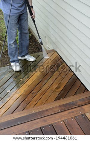 Man Spray Cleaning Deck - stock photo