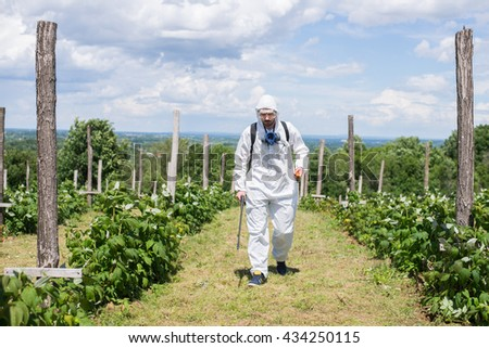 Man spraying chemicals on his raspberry field,colored and under exposed photo