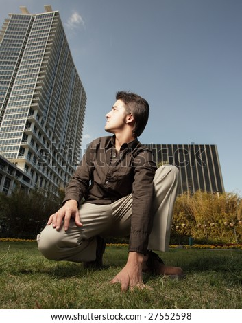 Man squatting and looking back at a tall building - stock photo