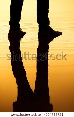 Man stand in the water with silhouette legs reflection. - stock photo