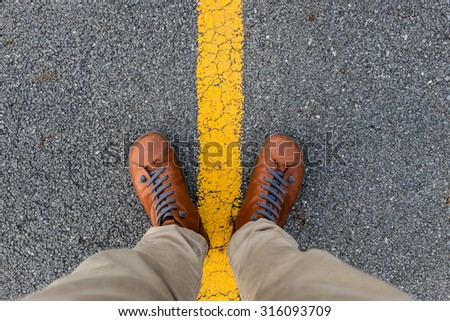 Man stand on asphalt road texture with yellow stripe - stock photo