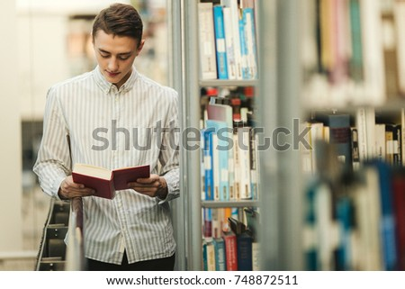 Man stand on the library and read book with blur background sun light