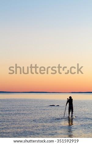 Man stand up paddling at sunset on Georgian Bay - stock photo