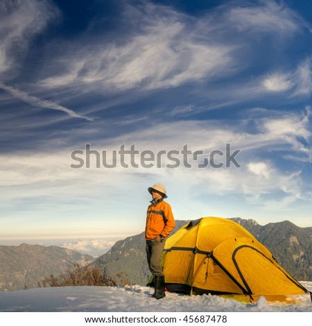 Man stand with yellow tent on snow hill against dramatic sky. - stock photo