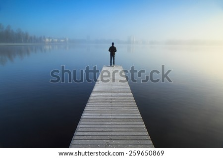 Man standing alone on the end of a jetty, looking over a foggy lake.