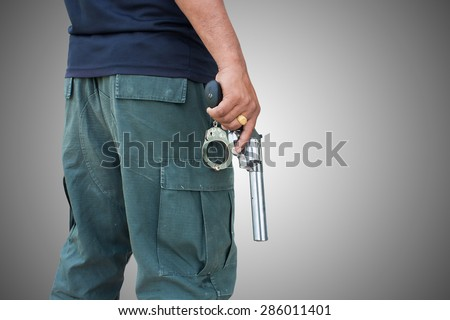 man standing and hand holding gun revolver ,side view on gray background - stock photo