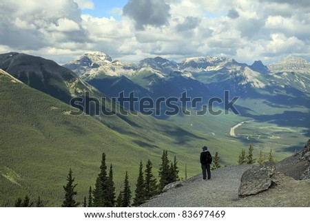 Man standing and looking at mountains from the top of Sulpher Mountain in Banff National park (Canada)