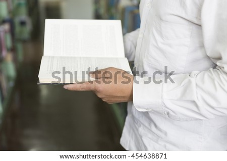 man standing and reading book on floor in aisle in library