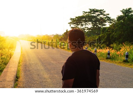 Man standing and thinking on a road looking Sunrise  . Concept of Vision to Success  - stock photo