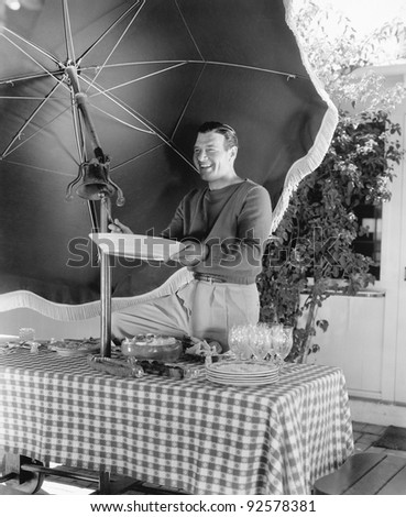 Man standing at a picnic table and holding a plate - stock photo