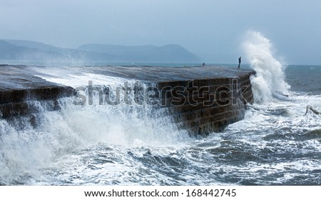 Man standing at the edge getting a big wave over him. - stock photo