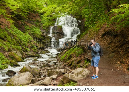 Man standing at the waterfall and making photos