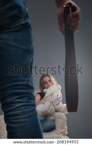 Man standing back to us and holding girdle in his hands looking at the young scared girl with black eye sitting on the chair and keeping big teddy bear. Isolated on grey background - stock photo