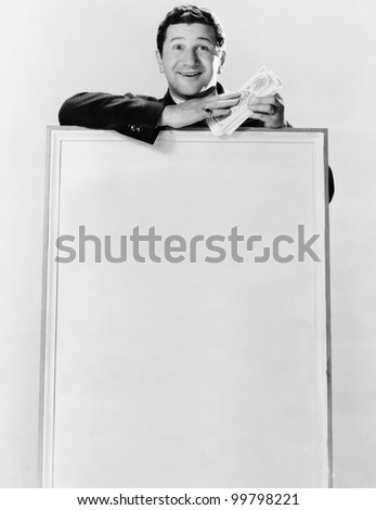 Man standing behind an information board and holding bundles of currency notes - stock photo