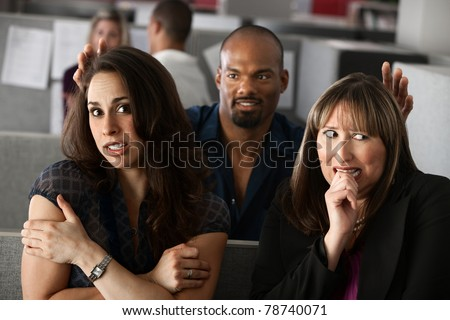 Man standing behind two scared women in office cubicle - stock photo