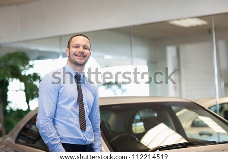 Man standing between cars in a dealership - stock photo