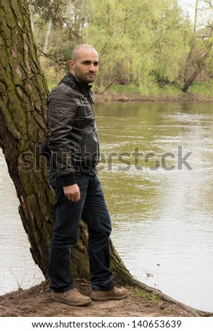 Man standing by a lake - stock photo