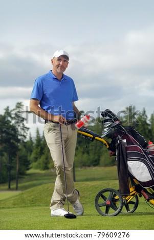 Man standing by golf bag full of sticks - stock photo