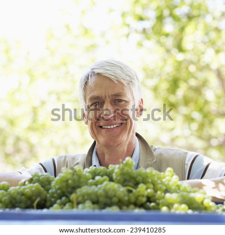 Man Standing by Grapes