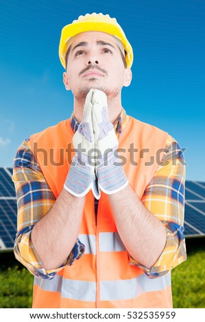 Man standing by solar panels and praying for great results with eco-friendly energy