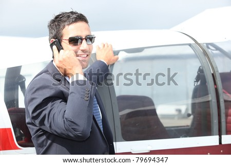 Man standing by the cockpit of a light aircraft talking on a cellphone - stock photo