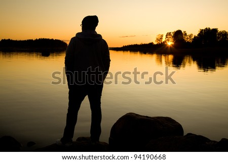 Man standing by the sea on sunset - stock photo