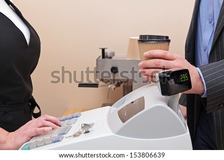 Man standing by the till in a coffee shop buying a takeaway drink in a paper cup. - stock photo