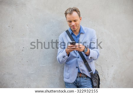 Man standing by the wall and using smartphone - stock photo