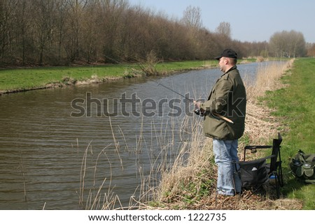 Man standing by the waterside with his fishing rod