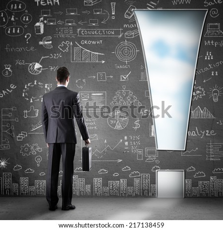 man standing front  a hole in wall in the form of an exclamation mark - stock photo