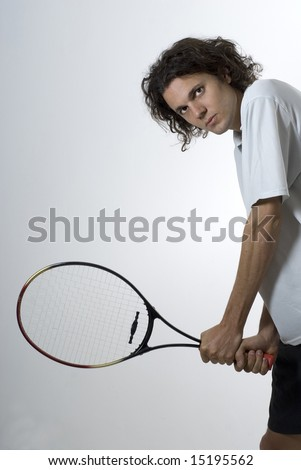 Man standing holding a tennis racket with a serious look on his face. Vertically framed photograph - stock photo