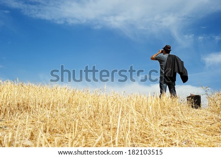 Man standing in a field watching with binoculars