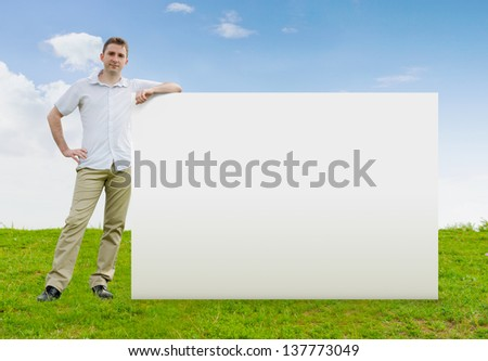 Man standing in a field with a large blank sign - stock photo