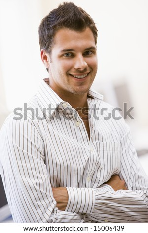 Man standing in computer room smiling - stock photo