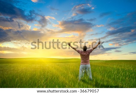 man standing in field, looking to the sunset - stock photo