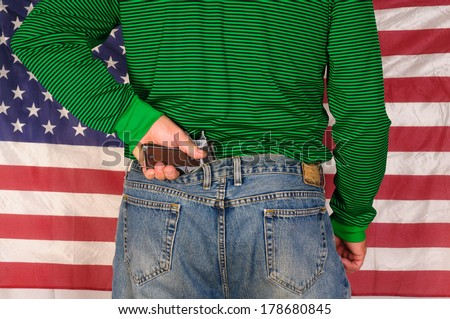 Man standing in front of a US flag holding the grip of a handgun which is stuck behind his back in his pants - stock photo