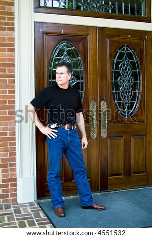 Man standing in front of beautiful wooden double doors with ornate glass work. - stock photo