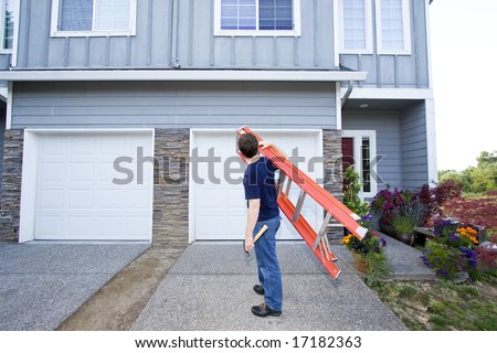 Man standing in front of house holding ladder and hammer. Horizontally framed photo. - stock photo