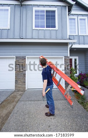 Man standing in front of house holding ladder and hammer. Vertically framed photo. - stock photo