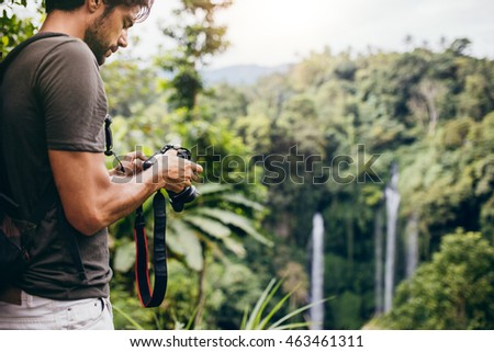 Man standing in front of waterfall with digital camera and checking the pictures. Male hiker photographing a water fall in forest