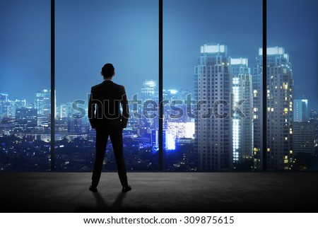 Man standing in his office looking at the city at night. Business success concept - stock photo