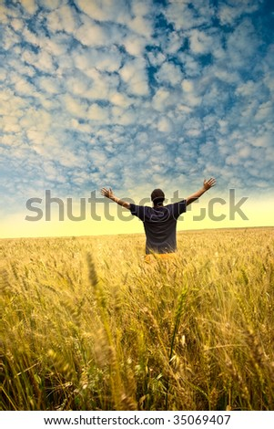 man standing in the field before sunset