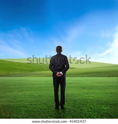 Man standing in the middle of a green meadow and observing the panorama in front of him - stock photo