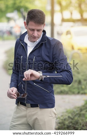 man standing in the street and looking at his watch