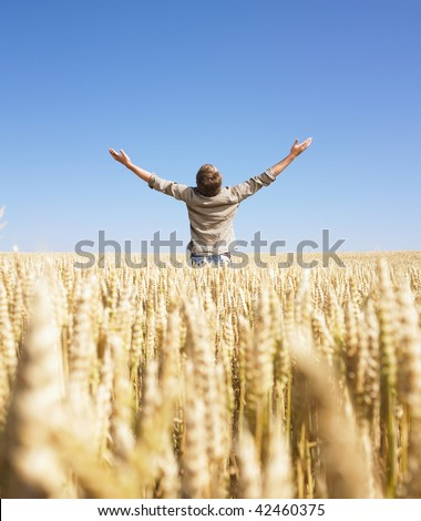 Man standing in wheat field with arms raised. Vertically framed shot. - stock photo